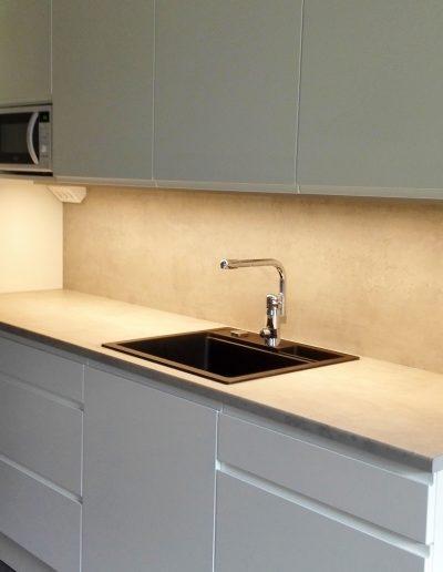 Keittiökaapit betonilaminaattitasolla, välitilalevyllä ja maalatulla vedinuraovella
